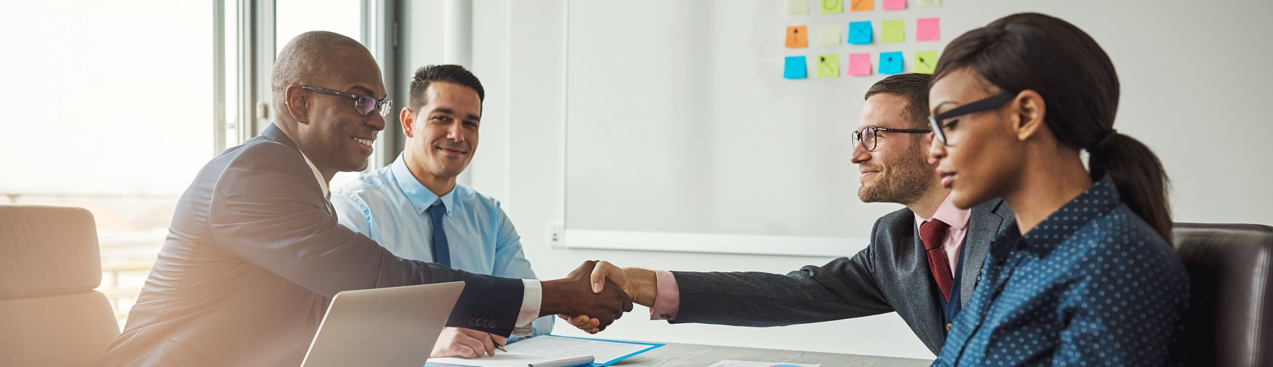 Business people shake hands over a conference table