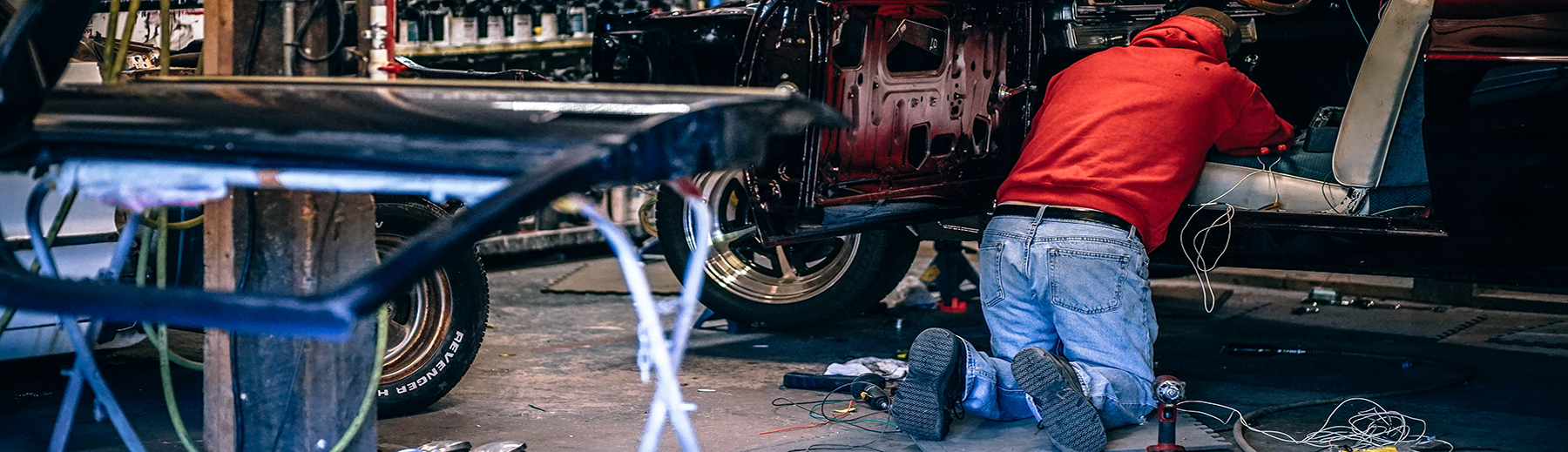 A mechanic works on a car in an autobody shop