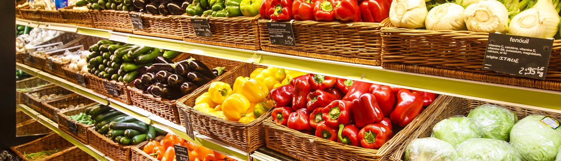Many types of fresh produce in baskets on shelves