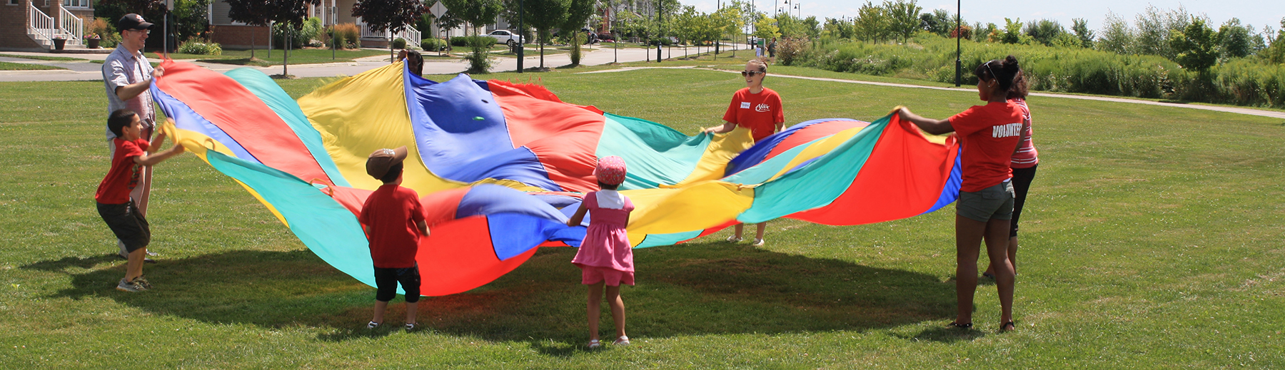 Children play with a large flag in a park