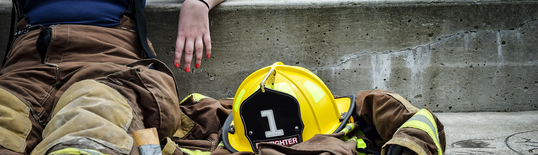 A firefighter rests beside her equipment