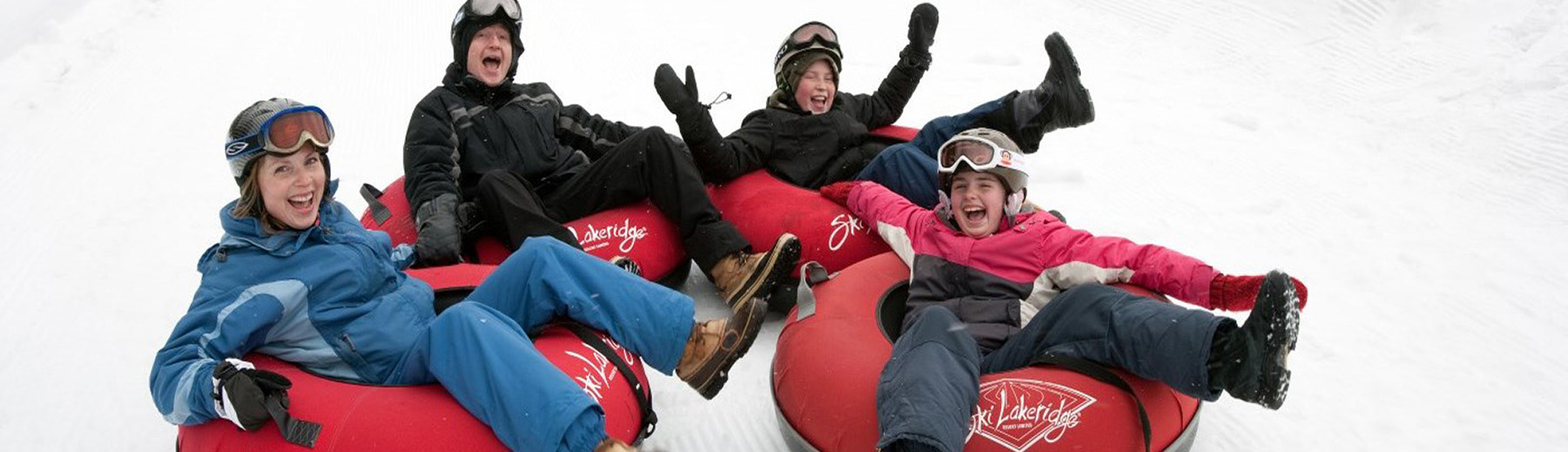 A family tubes down a snow covered hill