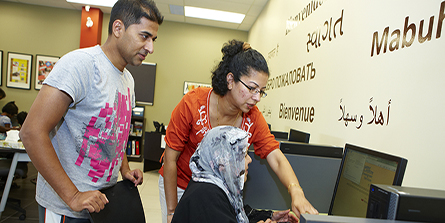 A volunteer shows a newcomer how to use a computer in the Welcome Centre