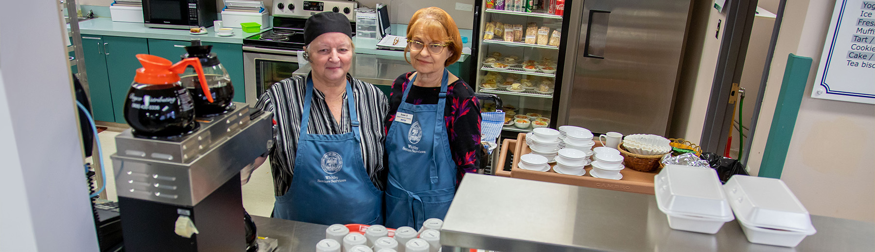 Two workers wear aprons behind a counter in a restaurant